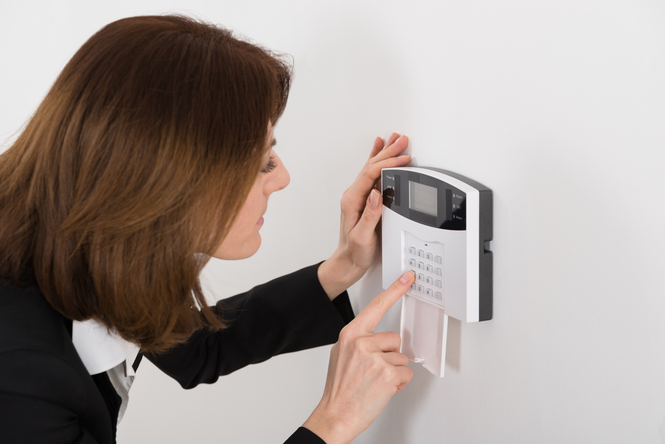Close-up Of Woman Entering Code In Security System